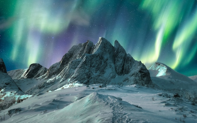 Aurora borealis over majestic mountain in snowy on segla island, norway