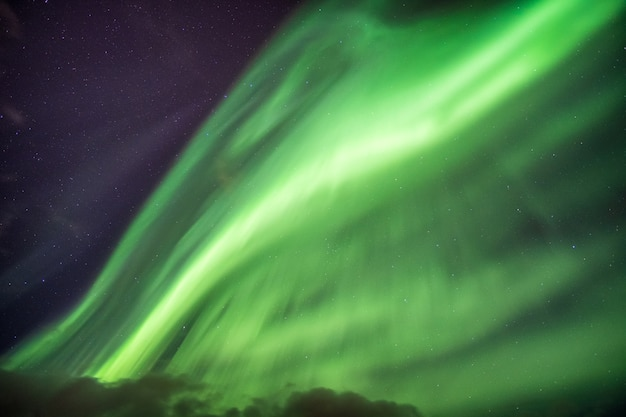 Aurora borealis (northern lights) explosion with stars on night sky at arctic