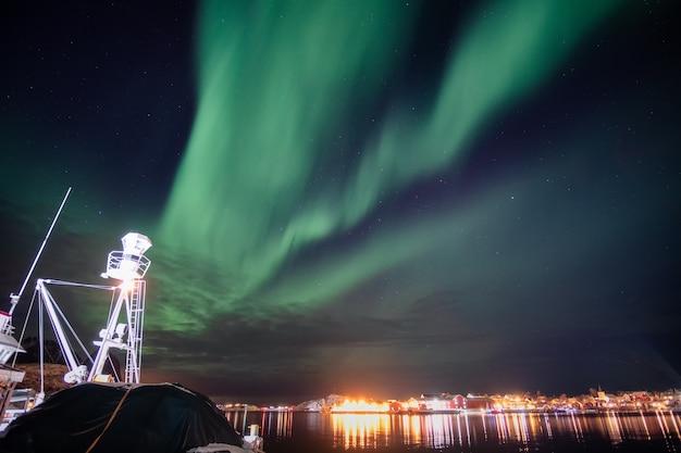 オーロラ、ノルウェー、ロフォーテン諸島の海岸線にある照らされたレーヌの町のオーロラ