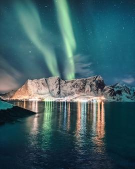 オーロラ、ノルウェー、ロフォーテン諸島のハムノイにある輝く村のある雪山の上のオーロラ