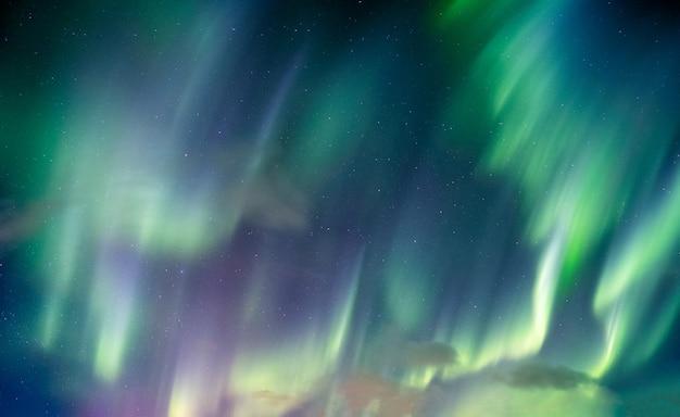オーロラ、北極圏の夜空に星と渦巻くオーロラ