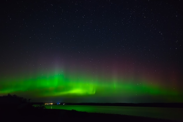 海岸沿いの街のオーロラ。湖の上の夜の星空のオーロラ。