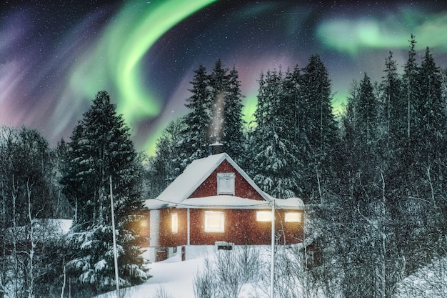 Aurora borealis over red nordic house with snow covered on winter at scandinavia