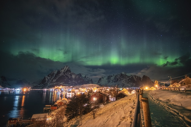 Aurora borealis over scandinavian village light shining in winter