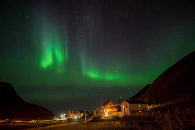 Aurora borealis above small village in lofoten, norway