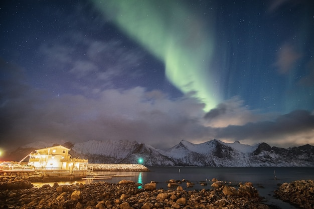 Aurora borealis on snowy mountain with light house at mefjord brygge