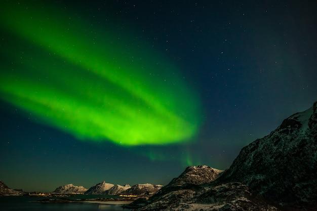 Aurora borealis in tromso, norway in front of the norwegian fjord