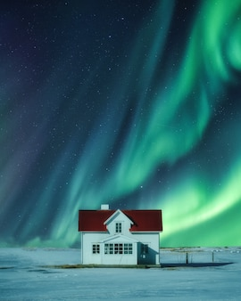 Aurora borealis over white house on snow in winter at scandinavia