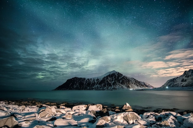 Aurora borealis with stars over mountain range with snowy coastline