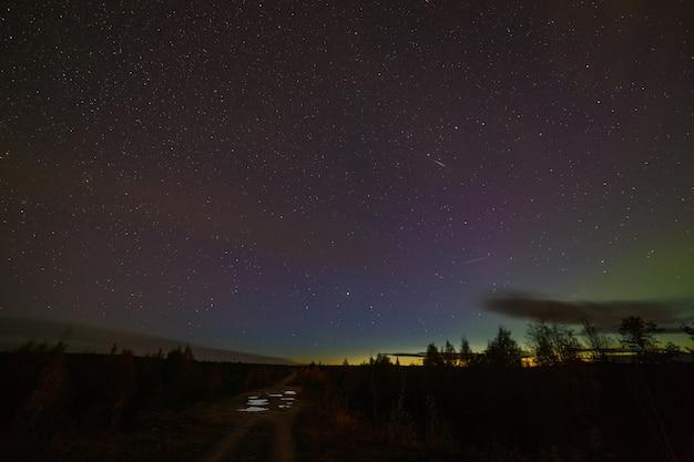 Аврора на ночном звездном небе. пейзаж на севере россии.