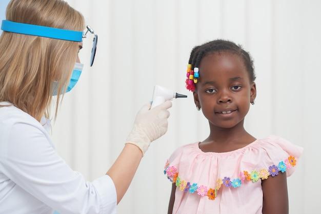 Женский доктор auscultating ухо маленького африканского ребенка.