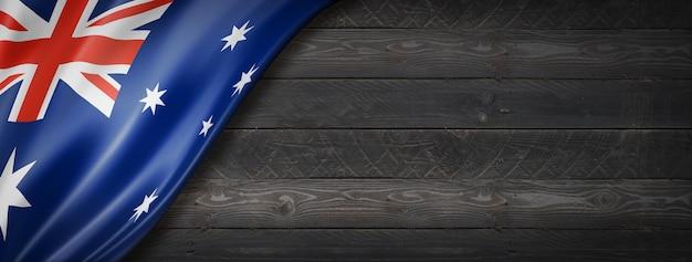 Australia flag on black wood wall. horizontal panoramic banner.