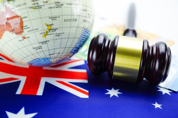 Australia flag and judge hammer with globe world map. law and justice court concept.