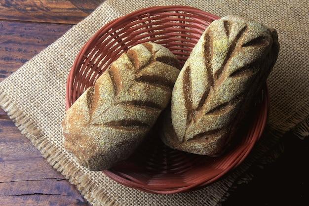 Australian bread loaf in basket over rustic wooden background