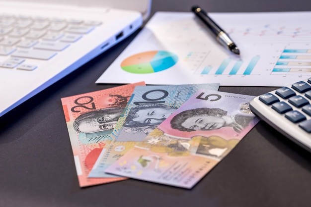 Australian dollar banknotes, laptop and diagram on black table