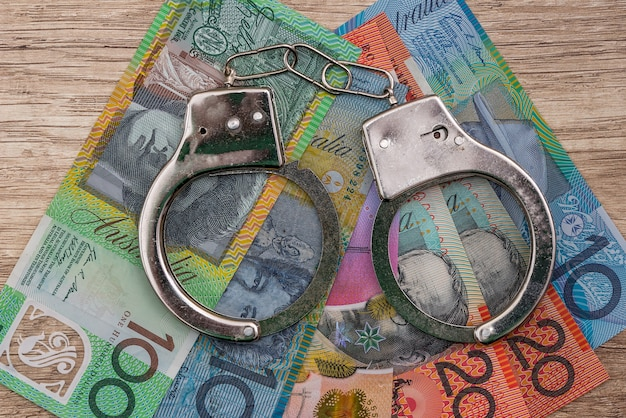 Australian dollar banknotes with handcuffs on wooden table