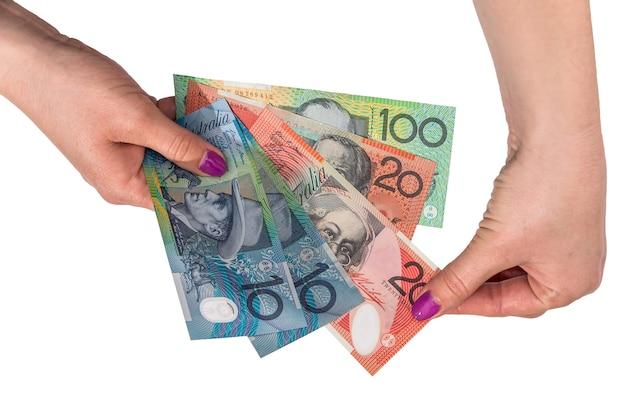 Австралийский доллар в руке женщины, изолированные на белом фоне
