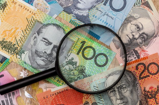 Australian dollar and magnifying glass. money concept