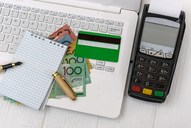 Australian dollar with terminal, laptop and notepad