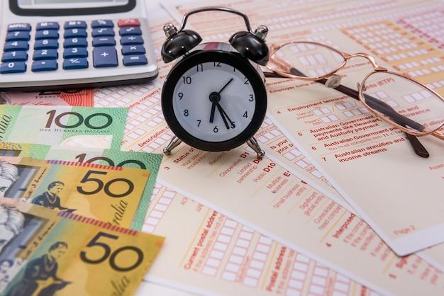 Австралийские доллары, часы и калькулятор в налоговой форме