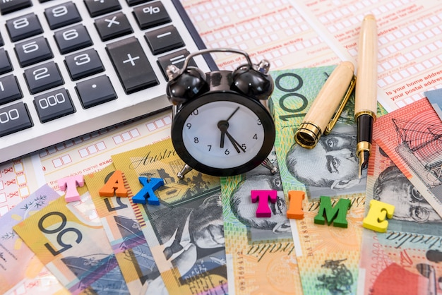 Australian dollars, clock and calculator on tax form