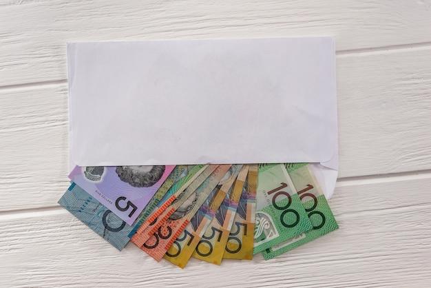 Australian dollars in envelope on wooden desk