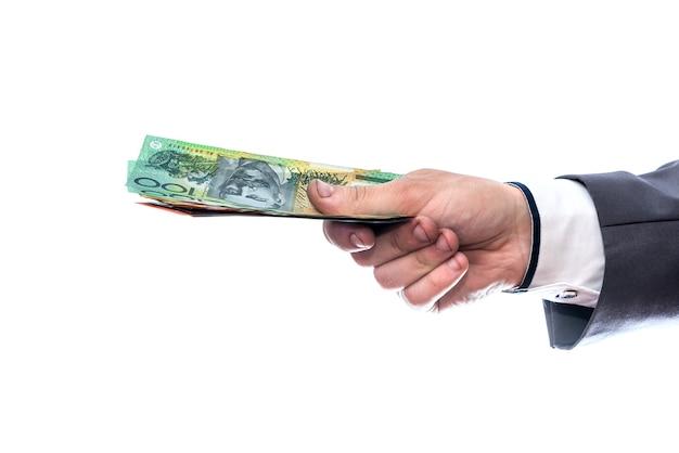 Австралийские доллары в мужской руке, изолированные на белом фоне
