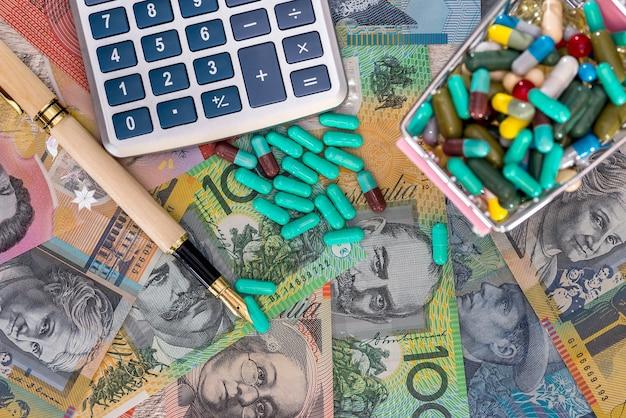 錠剤、ペン、電卓でいっぱいのカートとオーストラリアドル