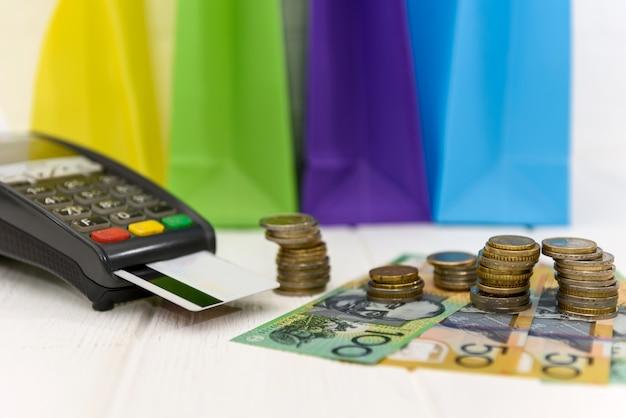 Австралийские доллары с монетами, терминалом и разноцветными сумками