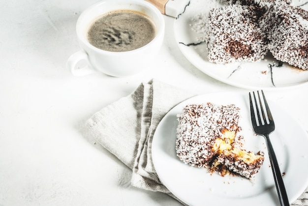 Australian food traditional dessert lamington - pieces of biscuit in dark chocolate sprinkled with coconut powder chips on a marble plate white table with coffee mug