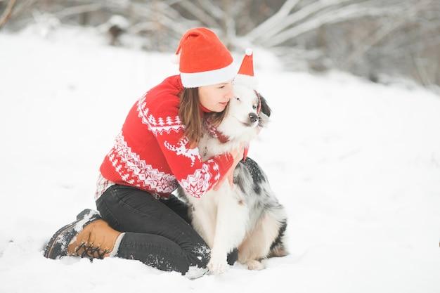 Australian shepherd in santa hat hugging with woman in winter forest