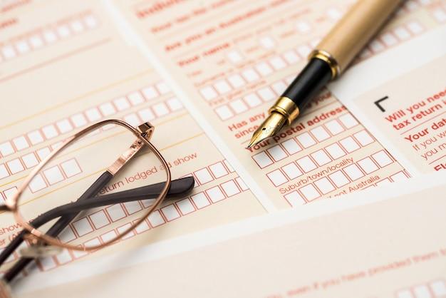 Австралийская налоговая декларация и ручка на деревянном столе