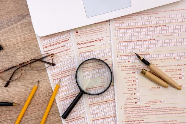 Австралийская налоговая форма с ручкой и блокнотом на столе