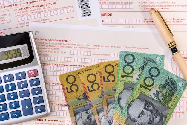 펜, 계산기 및 호주 달러가 포함 된 호주 세금 양식