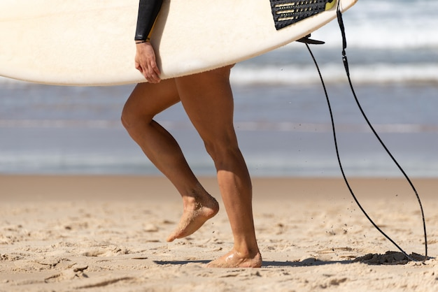 Australian woman surfer walking along the beach whit her surfboard. water deport concept.listro