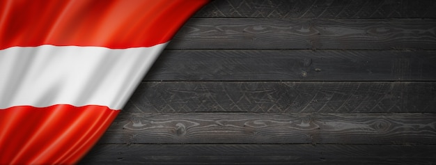 黒い木の壁にオーストリアの旗。水平方向のパノラマバナー。