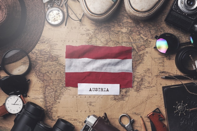 Austria flag between traveler's accessories on old vintage map. overhead shot