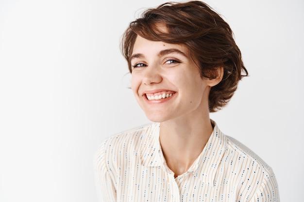 진실하고 솔직한 사람들. 짧은 헤어스타일을 한 블라우스를 입은 아름다운 젊은 여성, 행복한 미소, 흰 벽에 서 있는