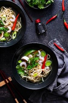 Authentic asian noodle soup in a black bowl