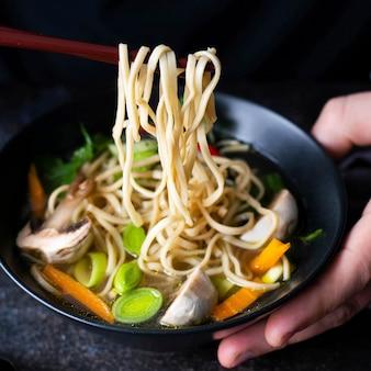 Autentica zuppa di noodles asiatica in una ciotola nera
