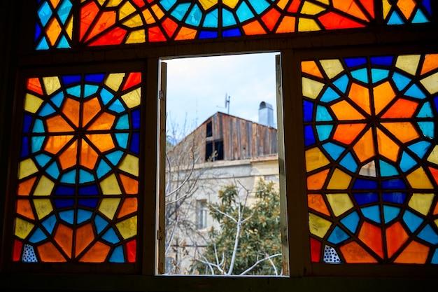 여러 가지 빛깔의 모자이크로 만든 스테인드 글라스 창문이 있는 오래된 주거용 건물의 정통 발코니. 조지아 트빌리시 - 2021년 3월 17일