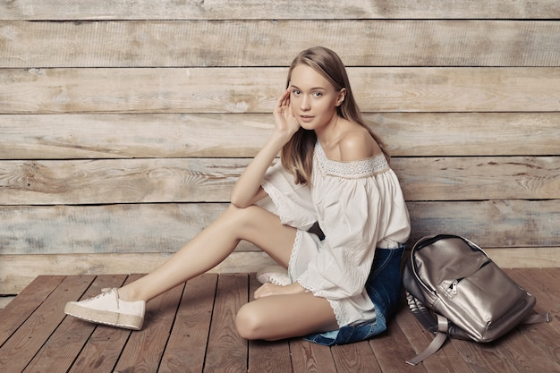 Authentic blonde young girl with silver backpack sitting wood wall
