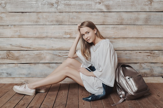 Authentic blonde young girl with silver backpack over wood wall