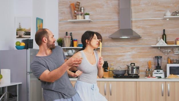 朝食時に台所用品を持ってパジャマで踊る本物のカップル。のんきな妻と夫が笑って楽しんで面白い人生を楽しんでいる本物の既婚者ポジティブ幸せな関係