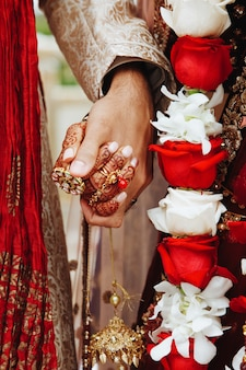 伝統的な結婚式の服装で一緒に保持している本格的なインドの花嫁と花groomの手