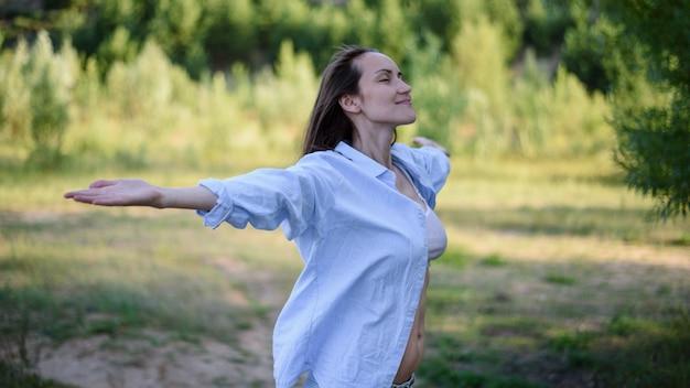 腕を広げて目を閉じて自然の中で青いシャツを着た笑顔の女性の本物の肖像画、自由飛行の概念の感覚