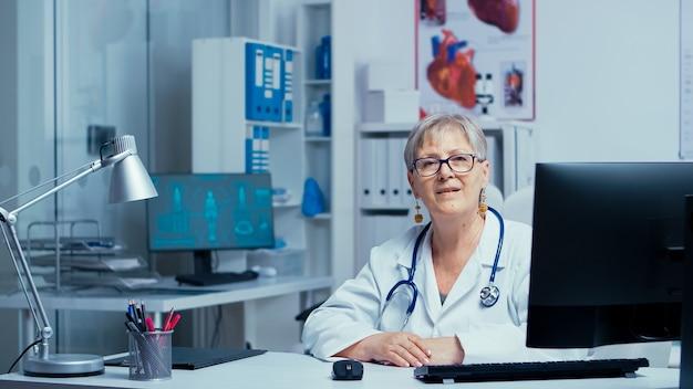 Аутентичный портрет опытного старшего врача, улыбающегося в камеру с медсестрой в фоновом режиме. кабинет врача современной частной больницы кабинет врача семейный терапевт