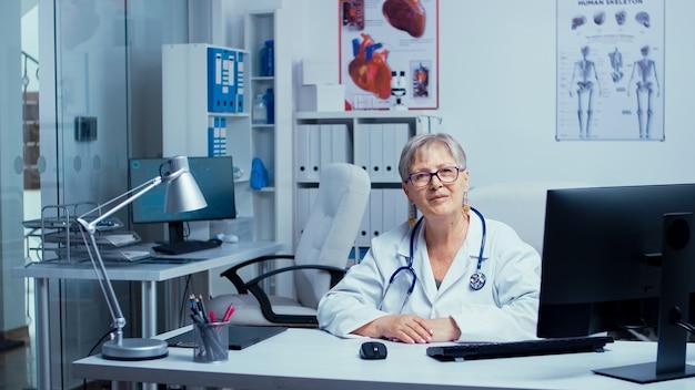 Аутентичный портрет старшего врача-женщины, улыбающегося в камеру, в то время как медсестра работает над компьютером в спине. современная частная клиника со стеклянными стенами. консультационный кабинет больницы