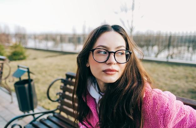 Подлинный портрет молодой кавказской женщины с волосами брюнетки в очках, сидя на скамейке в парке.