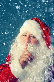 정통 산타 클로스. 산타 클로스가 손가락을 입술에 대고 있습니다. 크리스마스 이야기.